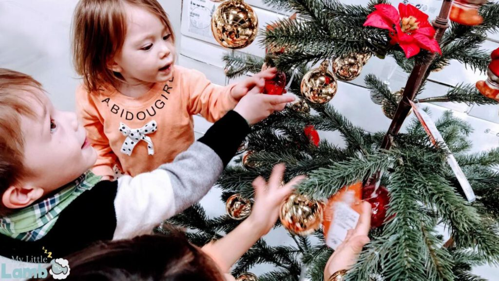 Little girl and little boy around the Christmas tree