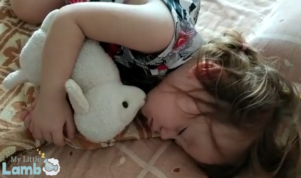 Little girl sleeping with My Little Lamb, a soft plushy toy with integrated audio player