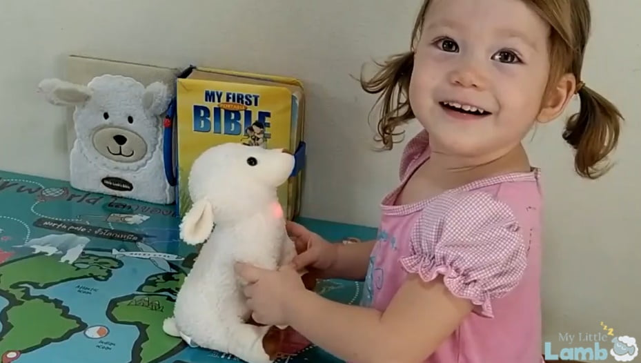 Little Girl playing with My Little Lamb, a plushie with integrated audio player