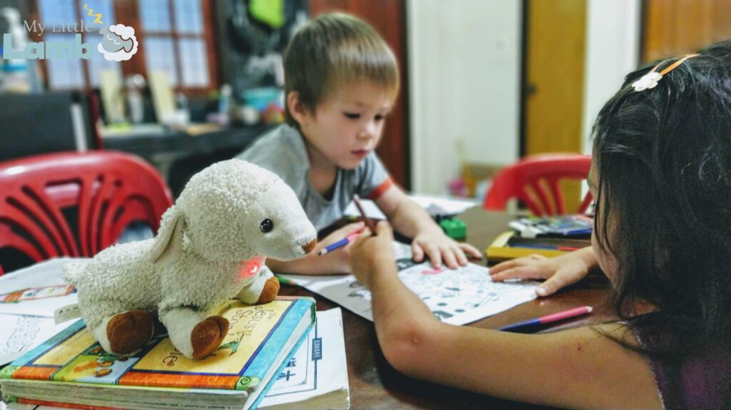 A boy and a girl studying with My Little Lamb,  a soft plushy toy with integrated audio player